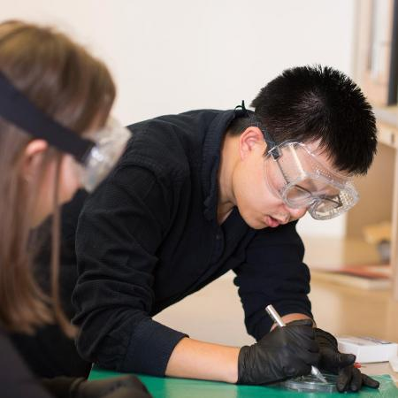 Bo Sun working in physics lab with student