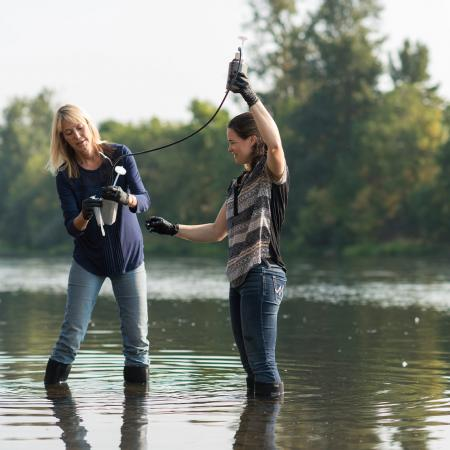 Kim Halsey and Cleo Davie-Martin collecting samples from a river.