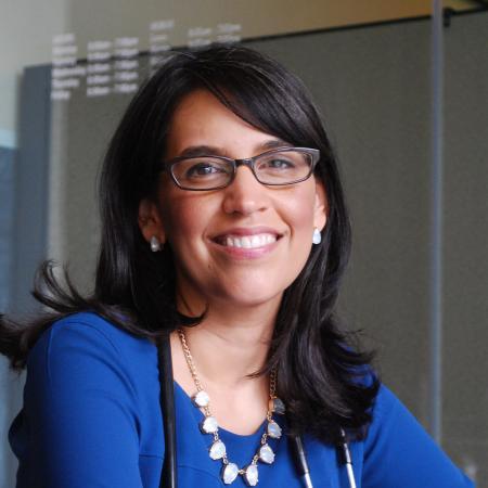 Dr. Eva Galvez sitting in office space.