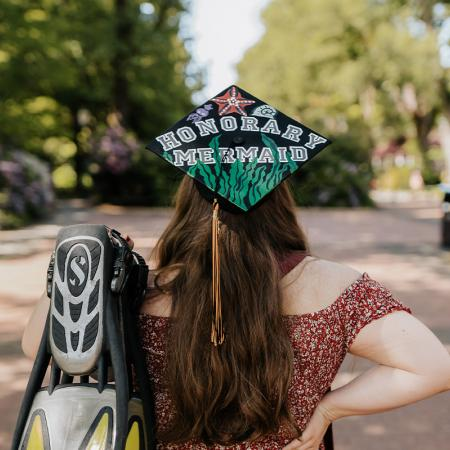 """Simone Burton facing away from the camera, holding her scuba fins and wearing her decorated grad cap that says """"Honorary Mermaid""""."""